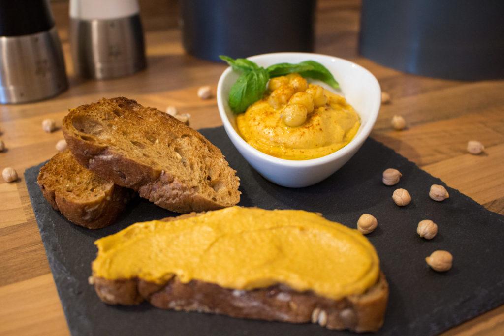 Eine Schale Hummus angerichtet mit Brot und getrockneten Kichererbsen auf einer Schieferplatte.