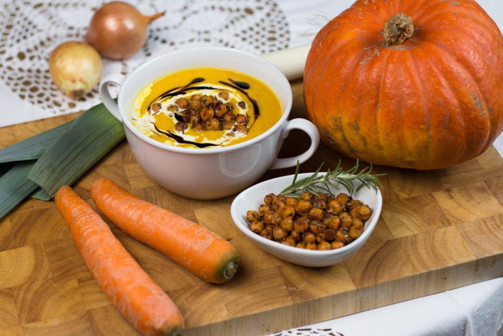 Kürbiscremesuppe mit gerösteten Kichererbsen, angerichtet mit Kürbis, Karotten und Lauch.