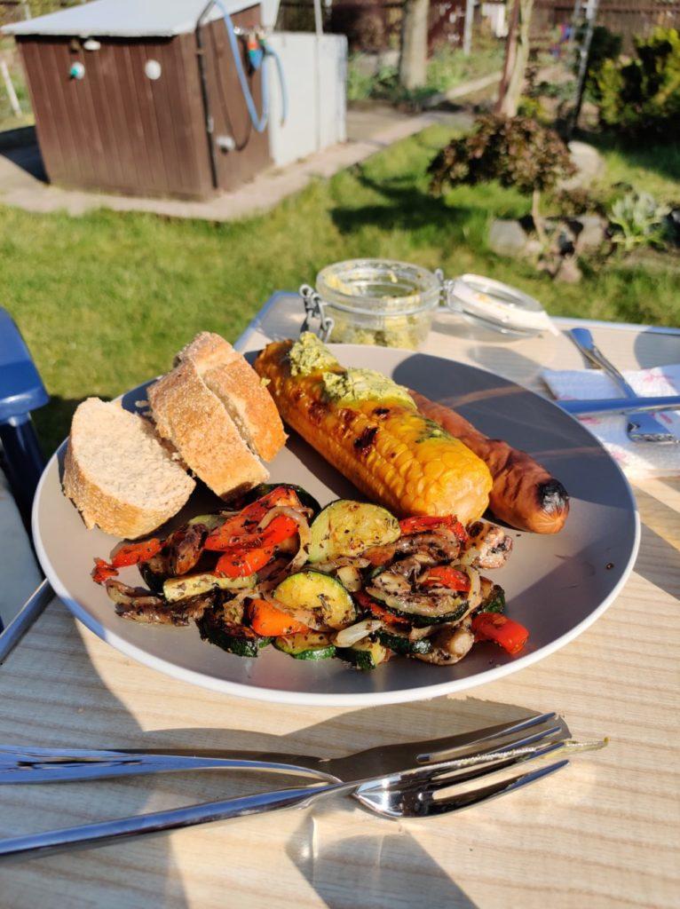 Grillteller mit Baguette, Maiskolben, Grillgemüse und Seitanwurst.