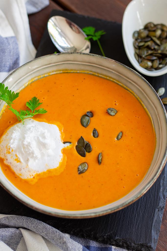 Einfach lecker: Vegane Tomaten-Kürbissuppe mit einem Klecks Pflanzensahne und gerösteten Kürbiskernen