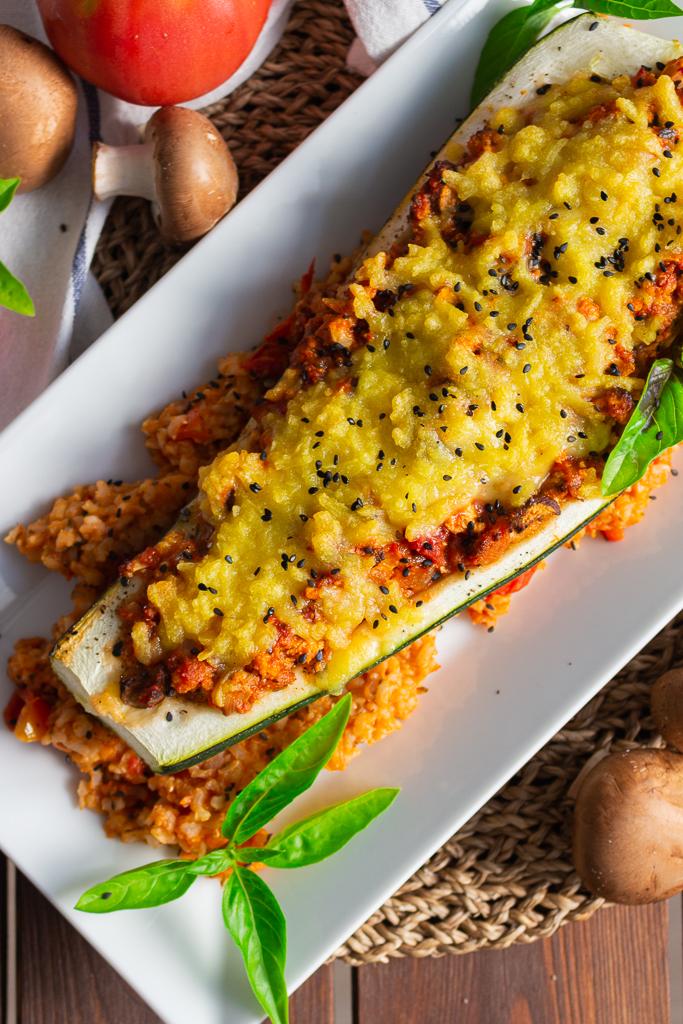 Leckere vegane gefüllte Zucchini auf einem Bett aus Tomatenreis. Garniert mit Basilikum und schwarzem Sesam auf einem länglichen weißen Teller.