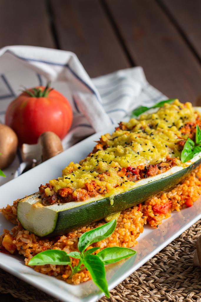 Vegane gefüllte Zucchini auf einem Bett aus Tomatenreis. Garniert mit Basilikum und schwarzem Sesam auf einem länglichen weißen Teller.