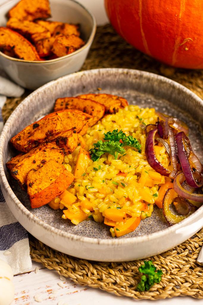 Veganes Kürbisrisotto mit gebackenem Kürbis und Zwiebelringen auf einer hellen Holzoberfläche