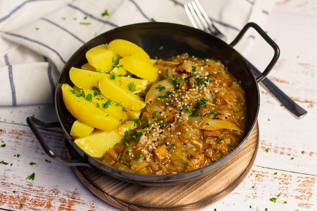 Eine leckere vegane Spitzkohlpfanne mit Salzkartoffeln in einer schwarzen Pfanne auf weißem Untergrund.