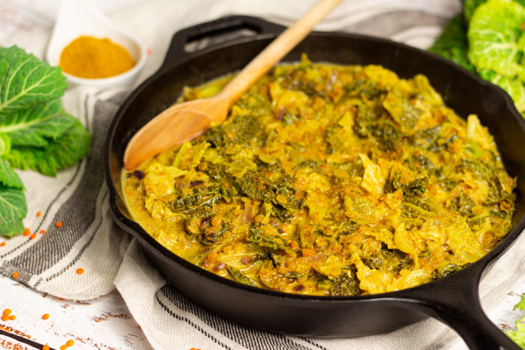 Veganes Wirsing-Curry mit roten Linsen in einer gusseisernen Pfanne