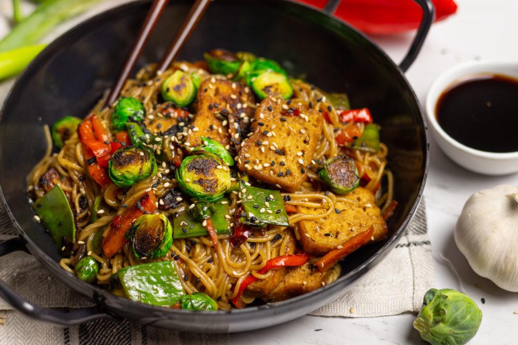 Asiatische Bratnudeln mit Austernsoße und Rosenkohl in einer schwarzen Pfanne