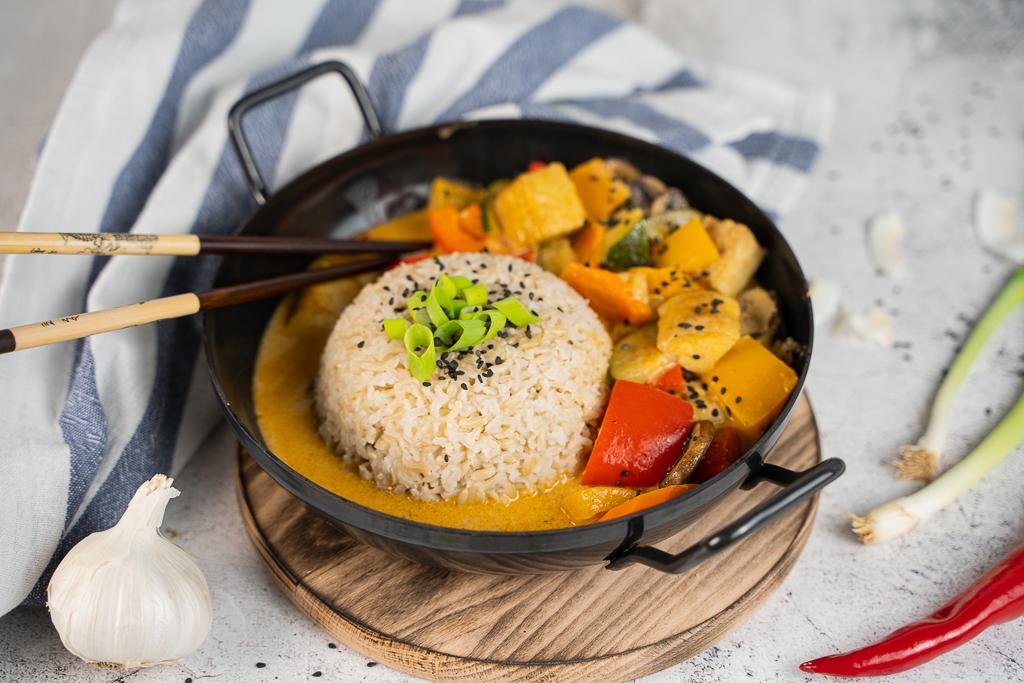Ein leckeres rotes Thai Curry mit Reis in einer schwarzen Pfanne.