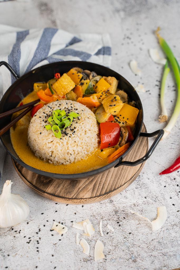 In ein Thai-Curry gehört viel buntes Gemüse, Kokosmilch sowie eine Curry-Paste. Das Ergebnis ist auf diesem Bild als leckeres Gericht mit einem Reis-Ball zu sehen.