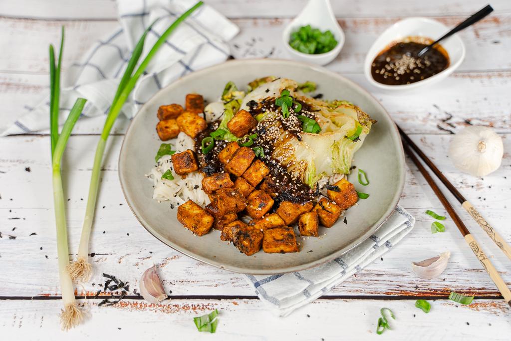 Leckerer gebackener Chinakohl mit krossem Tofu, Reisnudeln und Mirin-Dressing auf einem Teller