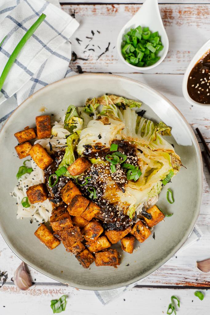 Chinakohl lässt sich schnell und einfach in 30 Minuten lecker zubereiten. Hier zu sehen mit goldbraunem Tofu, Lauchzwiebeln und einem dunklen Dressing.