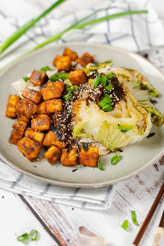 Herrlich krosser Tofu mit gebackenem Chinakohl und Soße. Angerichtet auf einem grünen Teller, umringt von Esstäbchen, Lauchzwiebeln und Knoblauch