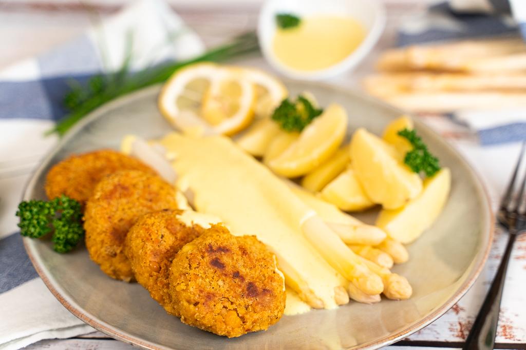 Spargel ist einfach gekocht. Perfekt serviert wird er mit einer veganen Hollandaise, leckeren Kartoffeln und knusprigen Bratlingen