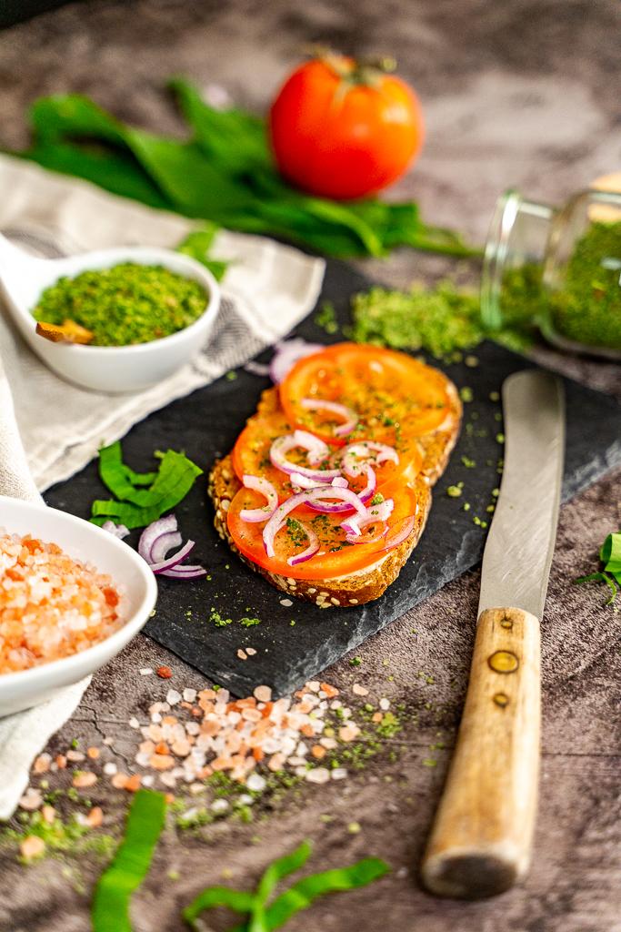Wie setzt man selbstgemachtes Kräutersalz am besten ein? Gut schmeckt es z.B. auf einem leckeren Tomatenbrot mit Zwiebeln.